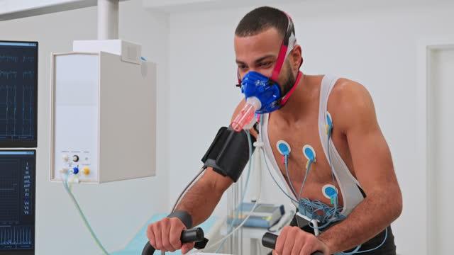 vidéos et rushes de athlète masculin de pan exécutant un essai spiroergometric sur un vélo à la clinique - effort