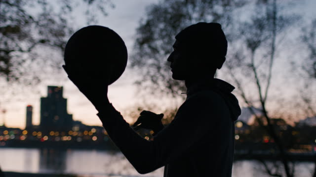 male athlete playing basketball on court at sunset - catching stock videos & royalty-free footage