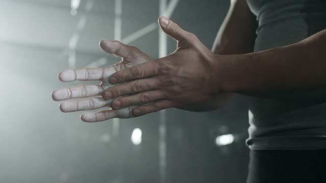 Mannelijke atleet krijt zetten met zijn handen in sportschool
