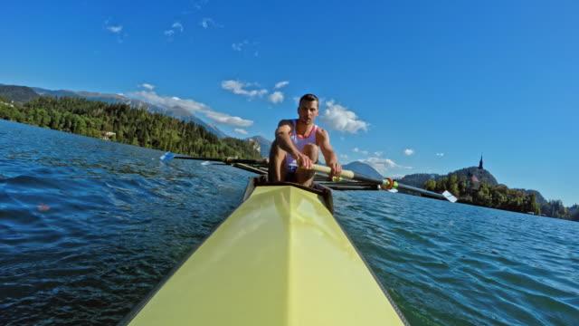 pov male athlete rowing across the sunny lake in a coxless pair - canottaggio senza timoniere video stock e b–roll
