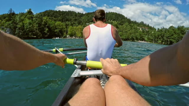 pov male athlete rowing behind his team mate across a sunny lake - rowing stock videos & royalty-free footage