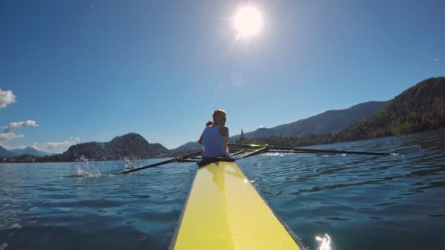 pov male athlete rowing in a coxless four on a sunny day - canottaggio senza timoniere video stock e b–roll