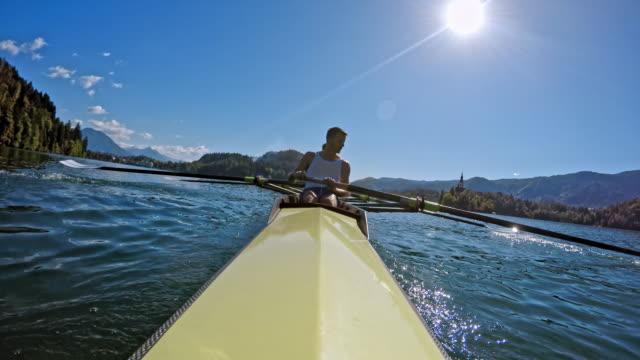 pov male athlete rowing in a coxless pair in sunshine - canottaggio senza timoniere video stock e b–roll