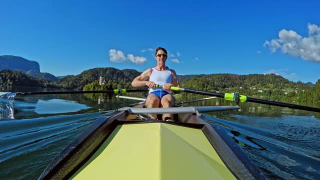 pov male athlete rowing in a coxless pair on a sunny day - canottaggio senza timoniere video stock e b–roll