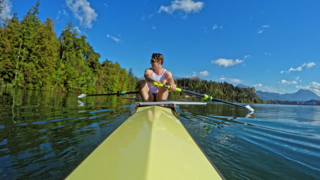pov male athlete rowing with his team mate in a coxless pair on a sunny day - canottaggio senza timoniere video stock e b–roll