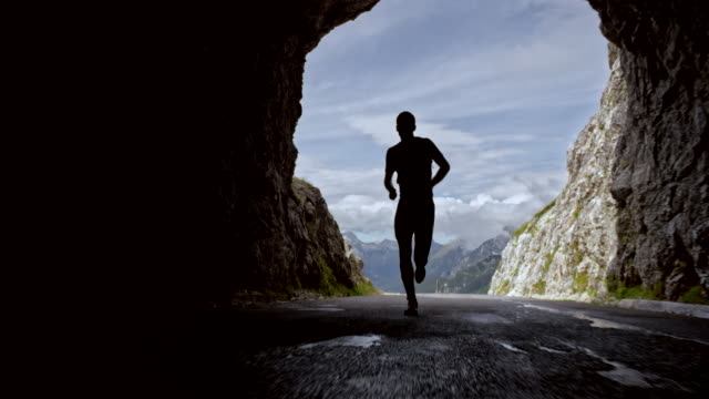slo mo male athlete running a marathon through a tunnel high in the mountains - arch architectural feature stock videos and b-roll footage