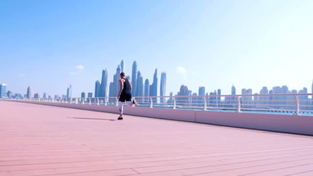 male athlete running in dubai marina - ethnicity stock videos & royalty-free footage