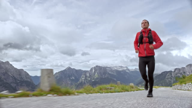 Male athlete running on a road high in the mountains on a cloudy day