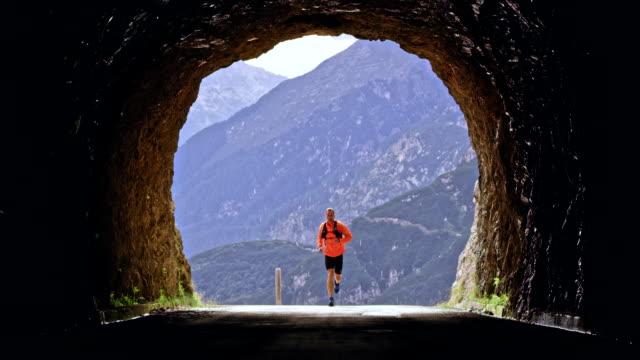 vídeos de stock, filmes e b-roll de atleta masculino ld correndo através de um túnel alto nas montanhas - força