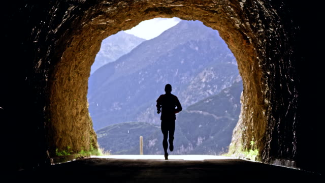 ld male athlete running through a tunnel in the high mountain range on a sunny day - tunnel stock videos & royalty-free footage