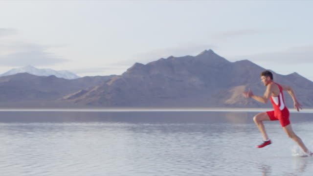 MS PAN Male athlete sprinting across lake with mountain range in background