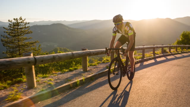 Male athlete standing while road cycling uphill at sunset