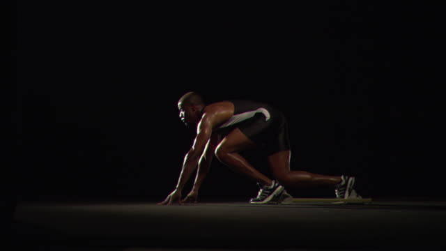 WS SLO MO Male athlete starting off running blocks / Los Angeles, California, United States
