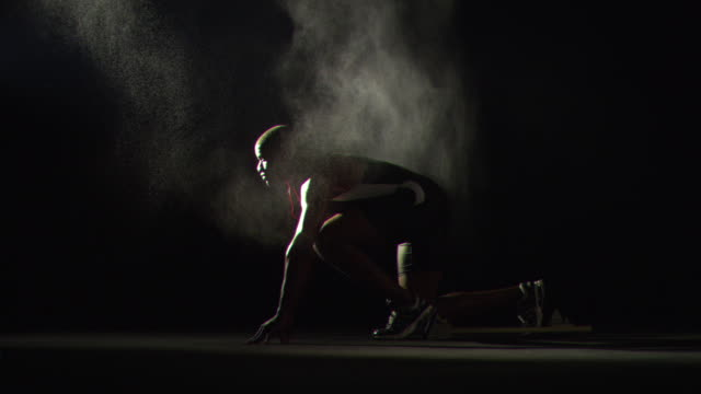 WS SLO MO Male athlete starting off running blocks with mist falling around / Los Angeles, California, United States