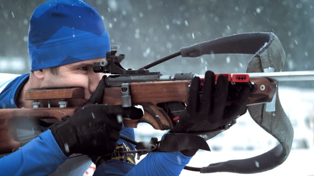 Male athlete taking shots with his biathlon rifle