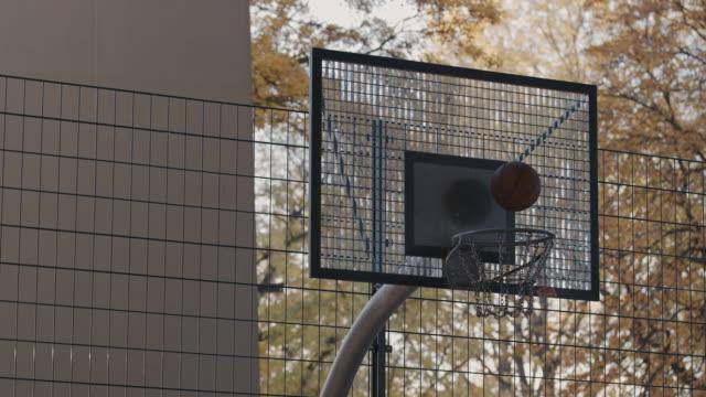 männlicher athlet werfen basketball in reifen auf platz - basketball stock-videos und b-roll-filmmaterial