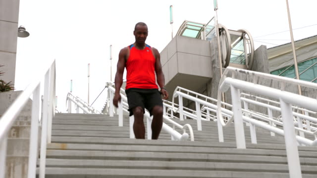 ms male athlete walking down stairs after running sets of stairs for morning workout - one man only stock videos & royalty-free footage