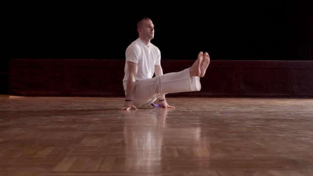 Männlicher Athlet Aufwärmen auf dem Boden und Capoeira Training vorbereiten.