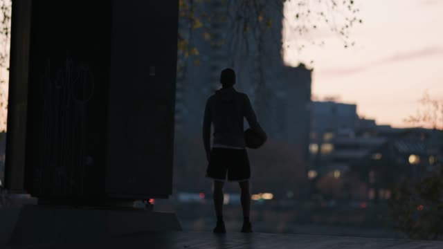male athlete with basketball hanging out in city - telecamera traballante video stock e b–roll