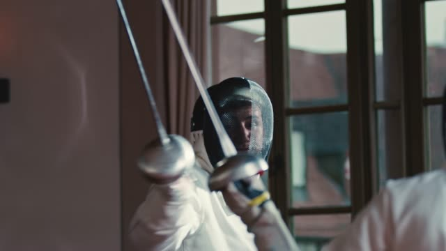 male athletes are fencing in castle - protezione video stock e b–roll
