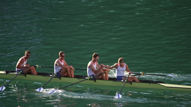 vídeos de stock e filmes b-roll de slo mo male athletes in a quad scull on a lake shaking hands - remar
