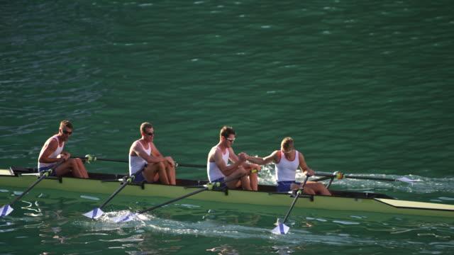 SLO MO männlichen Athleten in ein Quad Scull auf einem See Händeschütteln