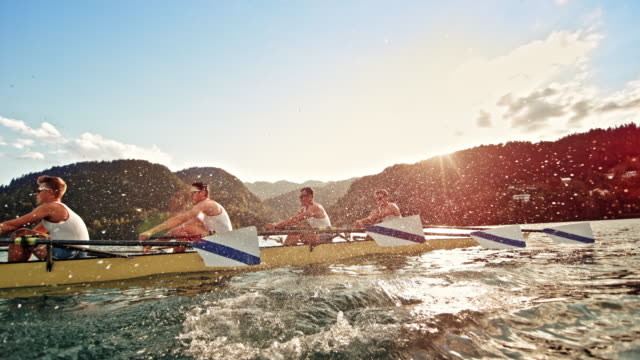 slo mo ts male athletes propelling a quad scull on a lake with sunshine in the background - realizzazione video stock e b–roll