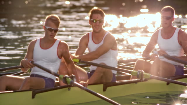 slo mo male athletes resting in their quad scull on a sunny lake - scull stock videos & royalty-free footage
