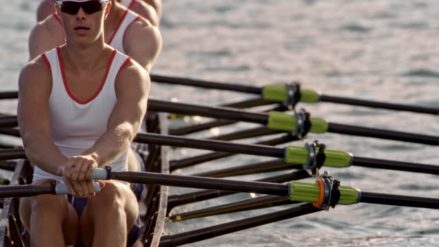 slo mo male athletes rowing across a sunny lake - rowing stock videos & royalty-free footage
