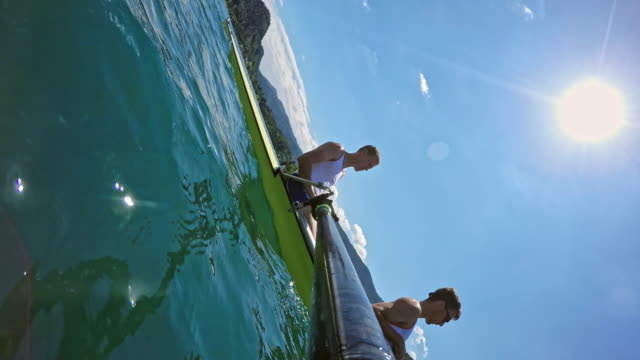 pov male athletes rowing in a coxless pair on a sunny day - canottaggio senza timoniere video stock e b–roll