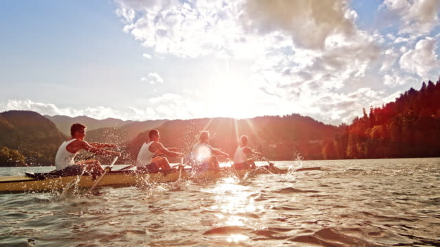 SLO MO Male athletes rowing on a lake in sunshine