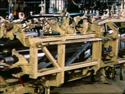 1959 male auto workers moving heavy machinery to reveal sleek blue car body on assembly line / chevy - 1950 1959 stock videos & royalty-free footage