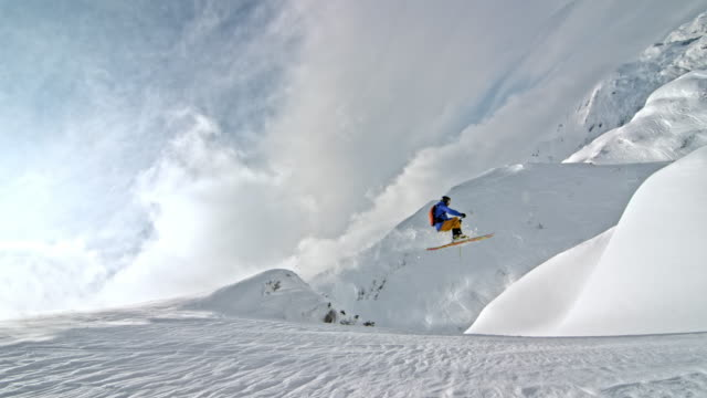 slo mo male backcountry skier jumping off a rock - skiing and snowboarding stock videos and b-roll footage