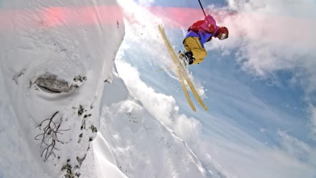 vídeos de stock e filmes b-roll de slo mo male backcountry skier jumping off a rock - saltar