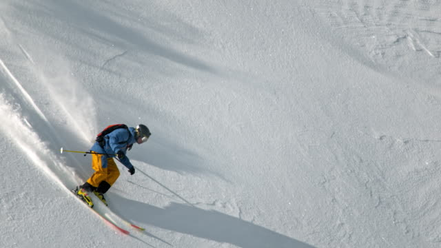 slo mo male backcountry skier skiing down the sunlit mountain - pulverschnee stock-videos und b-roll-filmmaterial