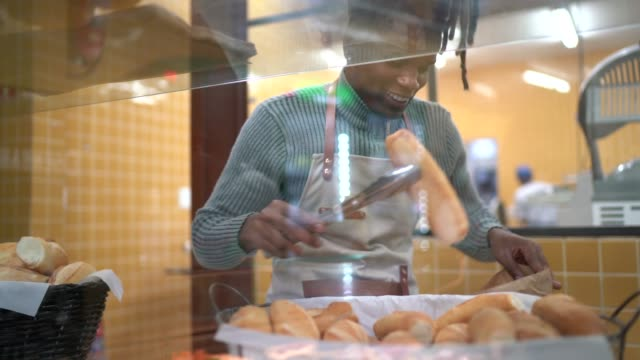 male baker putting breads inside a bag in the bakery - cestino video stock e b–roll