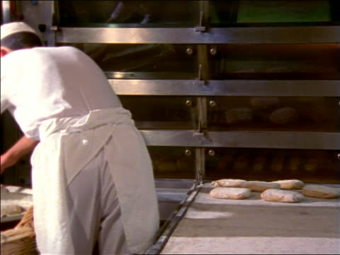 REAR VIEW male baker putting dough on tray near oven / France