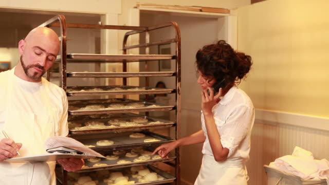 stockvideo's en b-roll-footage met ms tu td pan male baker writing an order and female baker talking on the phone / santa fe, new mexico, usa - draadloze telefoon