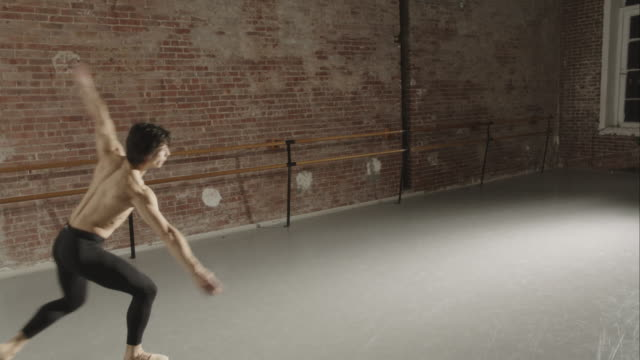 male ballet dancer practicing jump tours en l'air in dance studio - ballettstange stock-videos und b-roll-filmmaterial