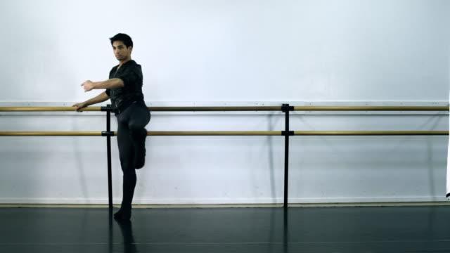 ws male ballet dancer warming up on bar / los angles, california, usa  - auf einem bein stock-videos und b-roll-filmmaterial