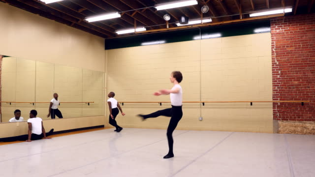 MS Male ballet dancer warming up while classmates stretch before practice in dance studio