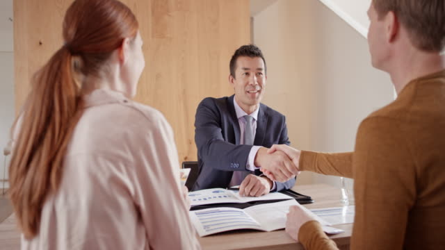 Male banker shaking hands with a couple visiting for consultation