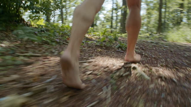 TS Male barefoot runner running in the forest on a sunny day