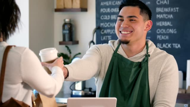 a male barista hands a customer her coffee as he smiles and talks with her. - ordering stock videos & royalty-free footage