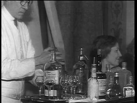 b/w 1933 male bartender mixing drink in shaker at portable bar in club / end of prohibition - 1933 stock videos & royalty-free footage