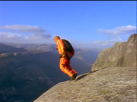 male base jumper wearing coveralls walking + jumping off edge of cliff / sweden - base jumper stock videos & royalty-free footage