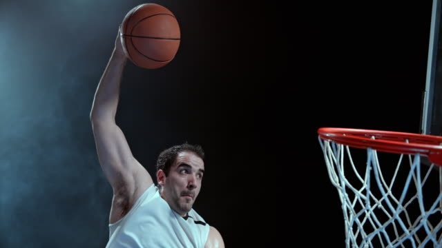 slo mo male basketball player doing a slam dunk - competizione video stock e b–roll