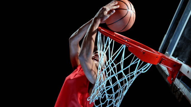 SLO MO Male basketball player in red t shirt doing a reverse dunk