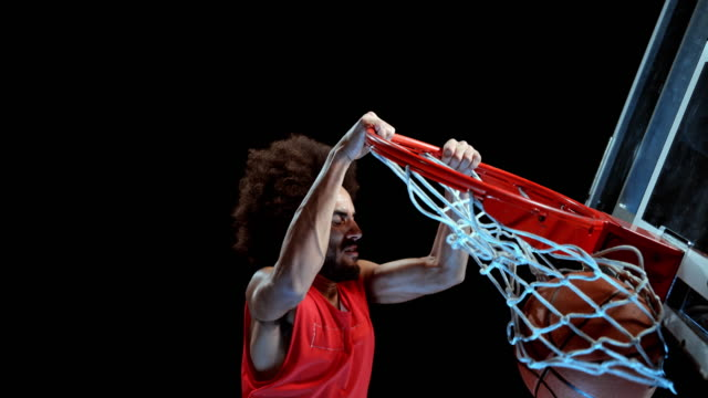 speed ramp male basketball player in red t shirt doing a slam dunk - shooting baskets stock videos and b-roll footage