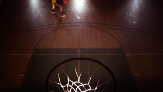 SLO MO HA CU Male basketball player performing a windmill slam dunk